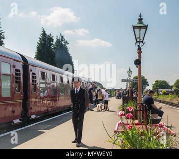 Sunny platform scene, families enjoying SVR heritage railway in the sun. Vintage diesel engine & carriages await departure. People come on & off train. - Stock Photo