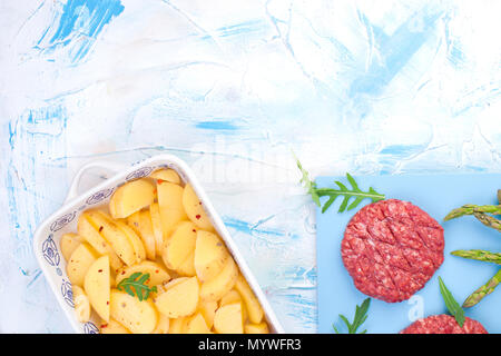 Raw cutlets from beef for barbecue and potatoes. Meat for cooking lunch and spices and asparagus. Background for text. flat lay - Stock Photo