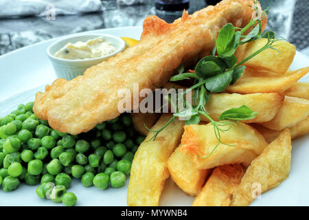 Crispy battered fish and chunky potato chips served with boiled green peas and mayonnaise, traditional English food . - Stock Photo