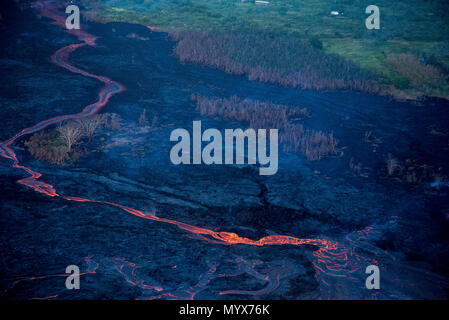 Leilani Estates, Hawaii, May 30, 2018 – Lava continues to flow east towards the Kapoho Bay area, bursting homes into flames and altering the landscape on the Big Island. Volcanic gas emissions remain very high from the fissure eruptions. At the request of the state, FEMA staff are on the ground to support local officials with life-saving emergency protective measures, debris removal, and the repair, replacement, or restoration of disaster-damaged publicly-owned facilities. Photo: Grace Simoneau/FEMA - Stock Photo