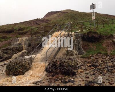 Flood water gushing down steps onto Cayton Beach - Stock Photo