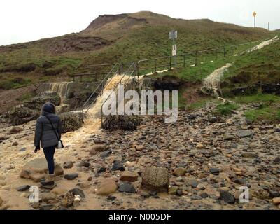 Flood water gushing down steps onto Cayton Beach - Stock Photo