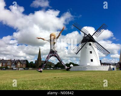 UK weather. Sunny day in Lytham St Annes in Lancashire. Girl has fun star jumping on Lytham Green in front of the - Stock Photo