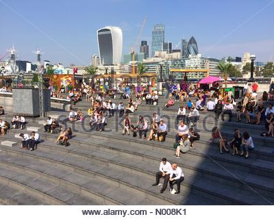 UK Weather, London, UK. 13th September 2016. People enjoying sunny weather on the Scoop outside City Hall. - Stock Photo