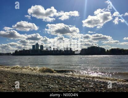 London, UK. 25th Apr, 2017. Blue sky and sunshine on the River Thames in London, seen behind the Canary Wharf financial - Stock Photo