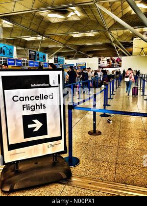 Passengers queue at the flight cancellations desk, as travel disruption continues to affect passengers at Stansted airport. - Stock Photo