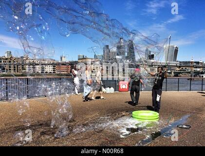 London, UK. 11th June 2018. A street entertainer blows giant bubbles at Bankside, London Credit: Patricia Phillips/StockimoNews/Alamy Live News Stock Photo
