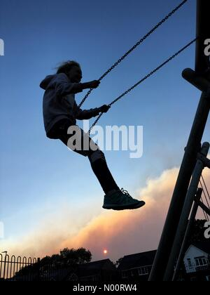 Rivington fire sends clouds of smoke over Adlington in Lancashire. Sun sets behind smoke cloud from fire on Winter Hill as girl swings in park. - Stock Photo