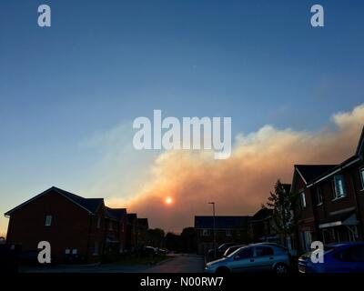 Rivington fire sends clouds of smoke over Adlington in Lancashire. Sun sets behind smoke cloud from moorland fire on Winter Hill. - Stock Photo