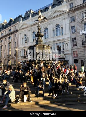 London, UK. 21st Oct 2018. People enjoying the October sunshine on Eros in Piccadilly Circus in central London. Credit: Andym/StockimoNews/Alamy Live News - Stock Photo