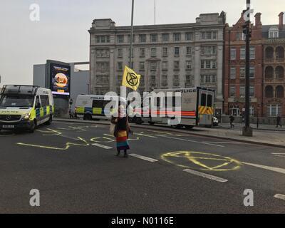 Waterloo Bridge, London, UK. 16th Apr 2019. Lone eco protester on Waterloo Bridge surrounded by police vans, April 16th, London Credit: PBurgess/StockimoNews/Alamy Live News