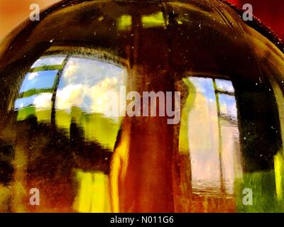 Ardara, County Donegal, Ireland. 09th June, 2019. Ireland weather. A sunny evening in Ardara, County Donegal. Reflection of landscape in a wine bottle from inside a cottage. Credit: Richard Wayman / StockimoNews/Alamy Live News - Stock Photo