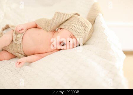 Cute newborn baby yawning, sleeping and wearing crocheted clothes. - Stock Photo