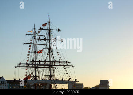 Tall Ships Race 2008. Bergen, Norway - August 2008 The UK flagged 'Stavros S Niarchos' (brig) arriving port in the evening, with crew in the masts. - Stock Photo