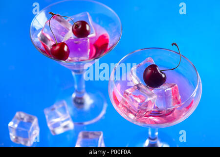 Cherry drink in cocktail glasses with ice cubes on a blue background. Refreshing cold drink with copy space. Summer beverage concept - Stock Photo