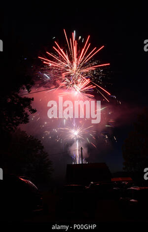 Colorful fireworks light up the night sky over a small town. - Stock Photo