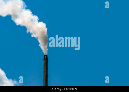 Air pollution from factory. Smoke from chimney of industrial pipe on clear blue sky. Greenhouse effect and global warming problem concept. Bad air qua - Stock Photo