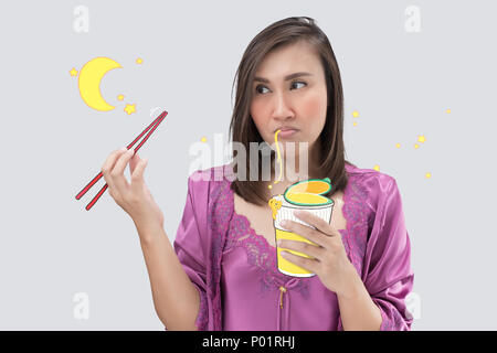 Asian woman in satin purple nightwear eating cup noodle at night. Female hungry at night on a gray background. Instant noodle. - Stock Photo