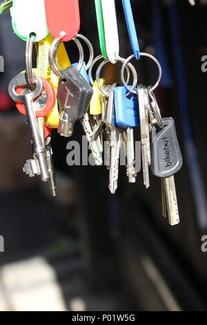A variety of silver keys hanging from colourful fobs against a black background - Stock Photo