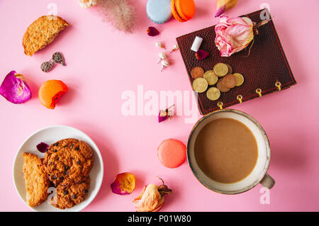 Flat lay of femenine things cookies coffee pearls flowers on a pknk background. Top view. - Stock Photo