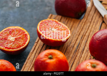 Whole and sliced fresh ripe  blood oranges on a wooden board. Close up - Stock Photo