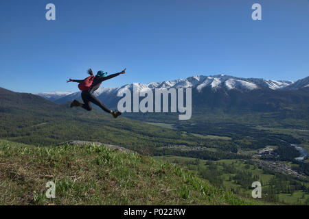 Jumping for joy at Kanas Lake National Park, Xinjiang, China - Stock Photo