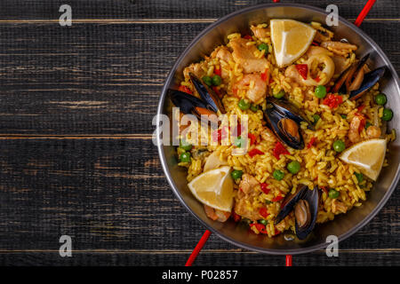 Paella with chicken,  seafood, vegetables and saffron served in the traditional pan, top view. - Stock Photo