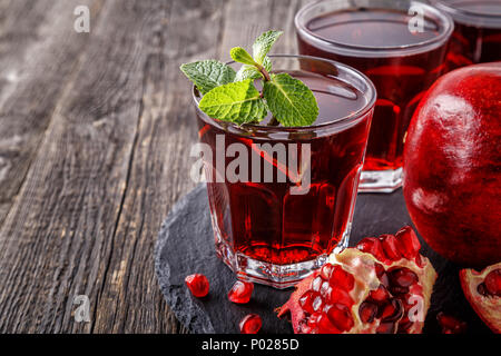 Glasses of pomegranate juice with fresh pomegranate fruits and mint on wooden table, healthy drink concept. - Stock Photo