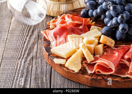 Prosciutto, wine, grape, parmesan on wooden table, selective focus. - Stock Photo