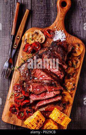 Beef steaks with grilled tomatoes, mushrooms and corn, top view. - Stock Photo