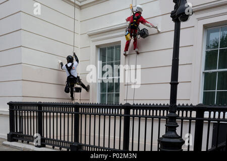Abseiling painters put a fresh coat of colour on the exterior of the Laneborough Hotel at Hyde Park Corner, on 8th June 2018, in London, England. - Stock Photo
