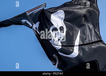 Pirate flag waving in wind against blue sky. Close up. - Stock Photo
