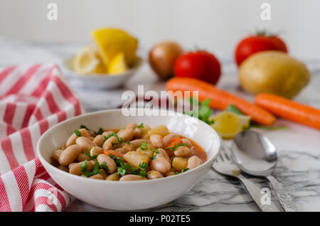 Red kidney beans in tomato sauce with carrot  in a white bowl,  closeup. horizontal view from above - Stock Photo