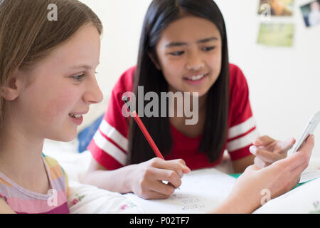 Two Girls Lying On Bed Using Mobile Phone To Help With Homework - Stock Photo