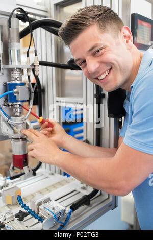 Portrait Of Male Engineer Working On Machine In Factory - Stock Photo