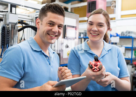Portrait Of Engineer And Apprentice Examining Component In Factory - Stock Photo