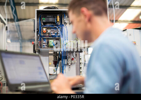 Male Engineer In Factory Using Laptop Computer - Stock Photo