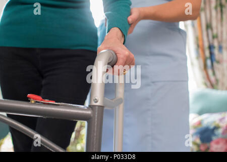 Senior Womans Hands On Walking Frame With Care Worker In Background - Stock Photo