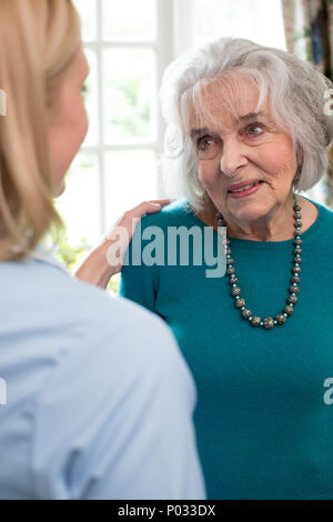 Care Worker Talking To Senior Woman At Home - Stock Photo