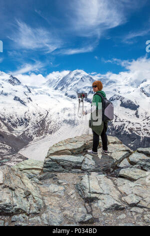Girl takes selfie photograph with selfie stick at Gornergrat at the end of the train ride from Zermatt, Switzerland, in the Alps - Stock Photo