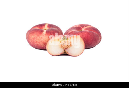 Two fresh red flat peaches with half cut on a white background - Stock Photo