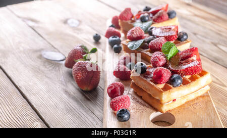 Viennese waffles with strawberry jam, fresh strawberries, raspberries, blueberries and chocolate chips on a wooden table. Delicious breakfast concept - Stock Photo