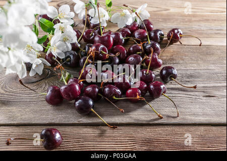 Fresh cherries and white cherry blossoms on a wooden background - Stock Photo
