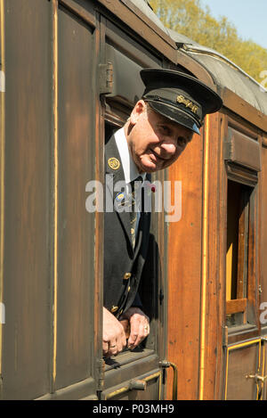 Portrait close up of gentleman ticket inspector on Severn Valley Railway, leaning out of carriage window in the sunshine, ready to greet passengers. - Stock Photo