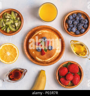 Pancakes with fruit, honey, maple syrup. Top view. - Stock Photo