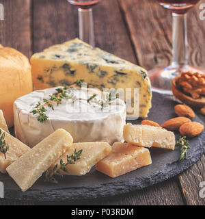 Cheese, nuts, honey and red wine on wooden background, selective focus. - Stock Photo