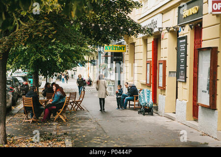Prague, September 24, 2017: The usual life of local residents in the Czech Republic. A group of people are sitting in a street cafe and talking, pedestrians are walking along the street. - Stock Photo