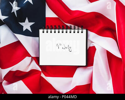 Notepad with an inscription on July 4th against the background of the US flag. Preparation for the Independence Day. Top view, close-up. The concept o - Stock Photo