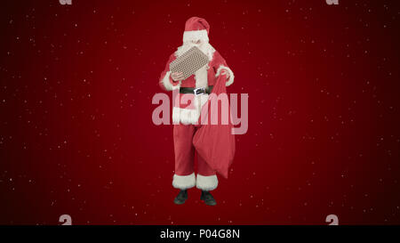 Santa Claus with his sack of lots of presents on red background with snow - Stock Photo