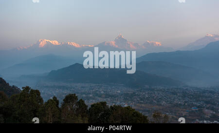 View of of the Machapuchare and the Annapurnas at sunrise from Sarangkot in Nepal - Stock Photo
